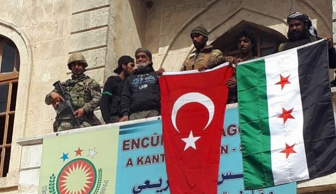 """A Turkish and a Turkey-backed Free Syrian Army soldier wave Turkish and FSA flags in the city center of Afrin, northwestern Syria, early Sunday, March 18, 2018. Turkey's President Recep Tayyip Erdogan said Sunday that allied Syrian forces have taken """"total"""" control of the town center of Afrin, the target of a nearly two-month-old Turkish offensive against a Syrian Kurdish militia, which said fighting was still underway. Erdogan said the Turkish flag and the flag of the Syrian opposition fighters have been raised in the town, previously controlled by the Kurdish militia known as the People's Defense Units, or YPG. (Hasan Krmzita/DHA-Depo Photos via AP)"""