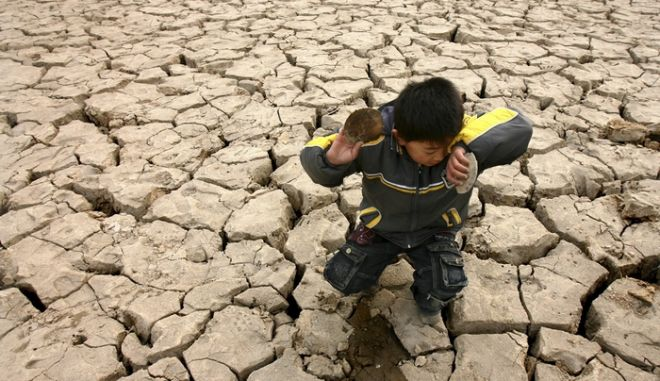 A child plays with dead clams on a dried-up riverbed on the outskirts of Zhengzhou, Henan province February 5, 2009. China has declared an emergency over a drought which could devastate crops and farmers' incomes, official media said on Thursday, threatening further hardship amid slumping economic growth.  REUTERS/Donald Chan (CHINA)