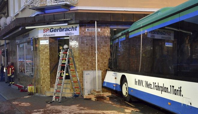 A bus sits in the facade of a building in Eberbach near Mannheim, southern Germany, Tuesday, Jan 16, 2018. Several students inside the school bus have been injured. (Rene Priebe/dpa via AP)