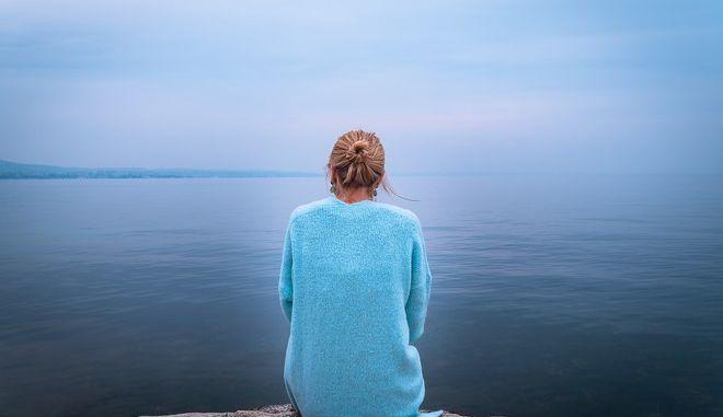 Γυναίκα θλιμμένη μπροστά από τη θάλασσα