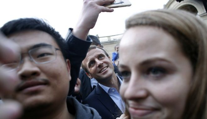 French President Emmanuel Macron poses for a selfie with a visitor in the Elysee presidential palace in Paris, Sunday, Sept. 17, 2017 as part of the 34th edition of France's heritage open days. The national buildings and administrations of France are open to the public for the Heritage Days weekend. (AP Photo/ Thibault Camus, Pool )