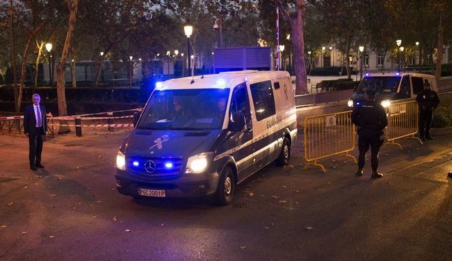 """Spanish national police officers cordon off an area as vans of the Civil Guard leave the National Court in Madrid, Thursday, Nov. 2, 2017. The defense lawyers of nine former members of the Catalan regional government ordered jailed by a Spanish court says the defendants are """"serene"""" and that they asked their lawyers to convey a call for calm to the people of Catalonia, and for any  protests over the jailings to happen """"without violence of any type."""" (AP Photo/Francisco Seco)"""
