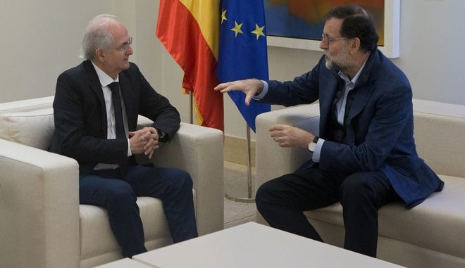 Former Caracas Mayor Antonio Ledezma, left, sits with Spain's Prime Minister Mariano Rajoy during a meeting at the Moncloa Palace in Madrid, Spain, Saturday, Nov. 18, 2017. The ousted mayor of Caracas pledged to spread his protest against Venezuela's socialist government across the world as he arrived in Spain on Saturday, a day after escaping from house arrest and slipping past security forces into Colombia. (AP Photo/Paul White)