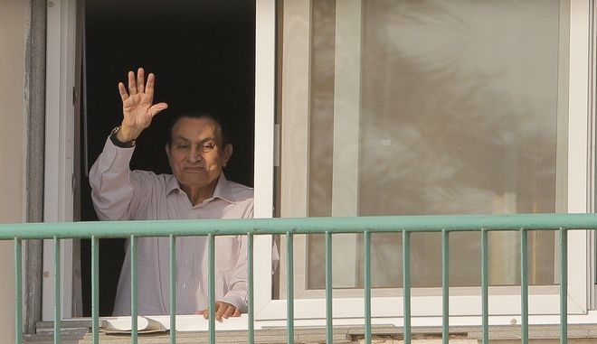 Ousted former Egyptian President Hosni Mubarak waves to his supporters from his room at the Maadi Military Hospital Thursday, Oct. 6, 2016, where he is hospitalized, as they celebrate the 43rd anniversary of the Oct. 6, 1973 war, when Egypt and Syria declared a war against Israel for the return of what they called their occupied lands, Sinai on the Egyptian front and Golan Heights on the Syrian Front. (AP Photo/Amr Nabil)