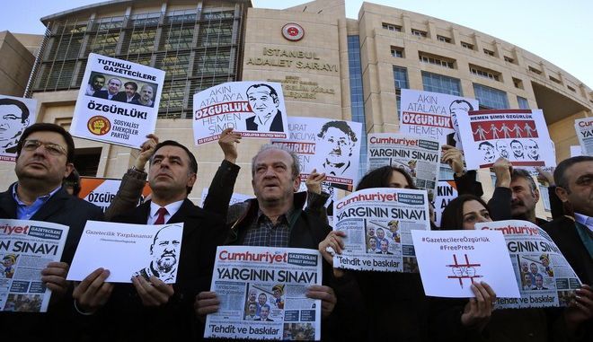 Demonstrators hold placards and copies of the Cumhuriyet daily newspaper as they stage a protest outside a court where the trial of about a dozen employees of the newspaper on charges of aiding terror groups, continues in Istanbul, Tuesday, Oct. 31, 2017. Most of them were released from prison earlier this month, but four of them, including editor-in-chief Murat Sabuncu and investigative journalist Ahmet Sik, are still in prison. (AP Photo/Lefteris Pitarakis)