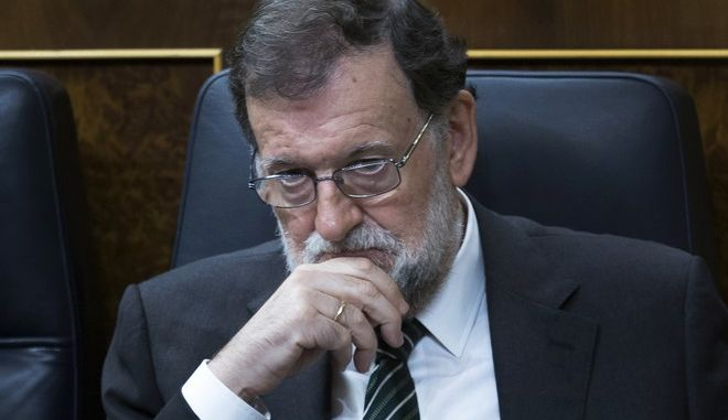 Spain's Prime Minister Mariano Rajoy listens to lawmakers during a parliamentary session at the parliament in Madrid, Wednesday, Oct. 18, 2017. About 50 Spanish and Catalan party lawmakers held up posters in the parliament demanding the release of two pro-Catalonia independence movement leaders, describing them as political prisoners. (AP Photo/Francisco Seco)