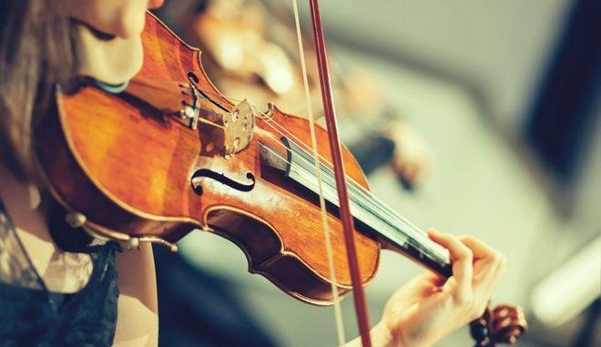 Μέλος συμφωνικής οχρήστρας παίζει βιολί.