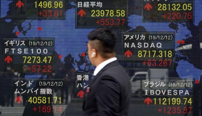 Άνδρας μπροστά σε πίνακα χρηματιστηριακών συναλλαγών
