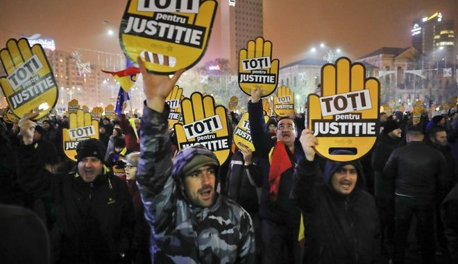 """People hold signs that read """"All for Justice"""" during a protest outside the government headquarters in Bucharest, Romania, Sunday, Nov. 26, 2017. Thousands of Romanians have gathered in Bucharest and other cities to protest against government plans to introduce legislation they say will weaken efforts to root out corruption. (AP Photo/Vadim Ghirda)"""