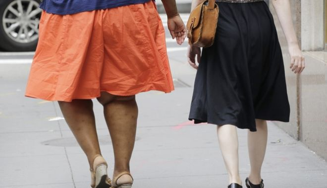 An obese woman, left, walks in New York, Monday, July 13, 2015. (AP Photo/Mark Lennihan)