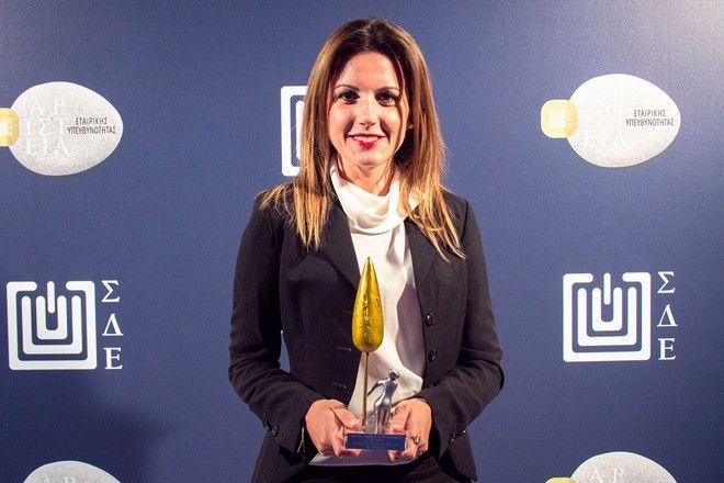 """Η Marketing & CSR Executive της Stoiximan κα Ιωάννα Κοζαδίνου κρατώντας στα χέρια της το """"Αριστείο"""" για το πρόγραμμα εταιρικής κοινωνικής ευθύνης """"Μικροί Ήρωες by Stoiximan""""."""