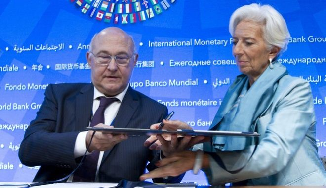 International Monetary Fund (IMF) Managing Director Christine Lagarde exchange documents with France's Finance Minister Michel Sapin after the Signing Ceremony 2016 Bilateral Borrowing Agreement at World Bank/IMF Annual Meetings at IMF headquarters in Washington, Saturday, Oct. 8, 2016. ( AP Photo/Jose Luis Magana)