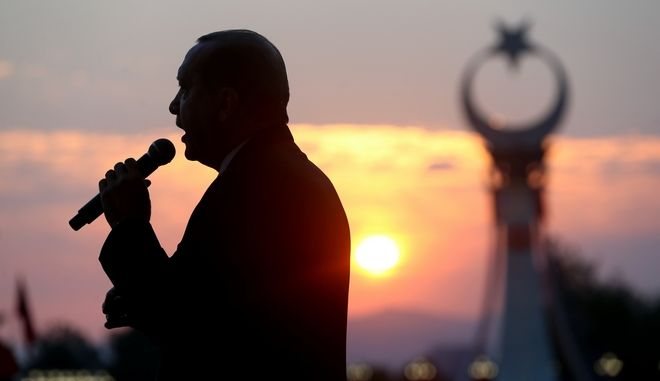 Turkey's President Recep Tayyip Erdogan delivers a speech to crowds outside the Presidential Palace, during the inauguration of a monument to commemorate the victims of the July 15, 2016 failed coup attempt, early Sunday, July 16, 2017 in Ankara, Turkey. Turkey marked the anniversary of the country's crushed military coup with a series of rallies and other commemorative events. (Presidency Press Service via AP, Pool)