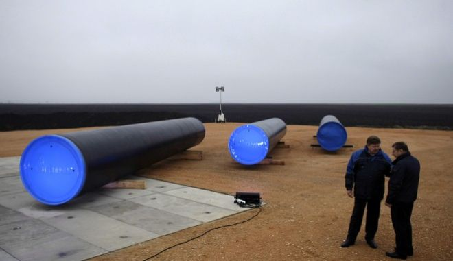 Two people stand next to the first section of the Gazprom South Stream natural gas pipeline in the town of Sajkas, 80 kilometers (50 miles) north of Belgrade, Serbia, Sunday, Nov. 24, 2013. Construction of the Serbian leg of the South Stream gas pipeline officially began on Sunday, Nov. 24, and, when finished, the pipeline is expected to ship up to 63 billion cubic meters (2 trillion cubic feet) of gas annually to Bulgaria, Serbia, Hungary, Slovenia, Austria and Italy in one leg and Croatia, Macedonia, Greece and Turkey in a second. (AP Photo/ Marko Drobnjakovic)