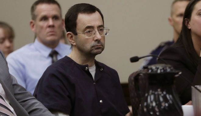 """Larry Nassar sits during his sentencing hearing Wednesday, Jan. 24, 2018, in Lansing, Mich.  The former sports doctor who admitted molesting some of the nation's top gymnasts for years was sentenced Wednesday to 40 to 175 years in prison as the judge declared: """"I just signed your death warrant.""""  The sentence capped a remarkable seven-day hearing in which scores of Nassar's victims were able to confront him face to face in the Michigan courtroom.  (AP Photo/Carlos Osorio)"""