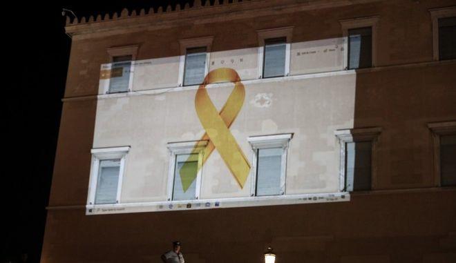 """Η Βουλή των Ελλήνων φώτισε την πρόσοψη του κτιρίου του Κοινοβουλίου με τη """"Χρυσή Κορδέλα"""", που αποτελεί το σύμβολο της μάχης κατά του καρκίνου στα παιδιά και τους εφήβους."""