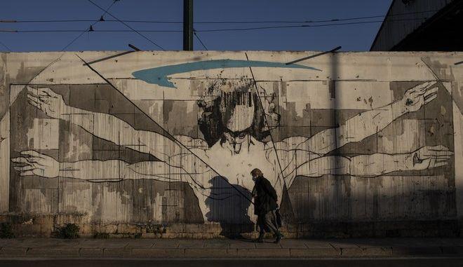 Ηλικιωμένη γυναίκα με μάσκα μπροστά από γκράφιτι στην Αττική.