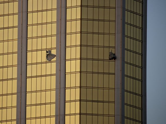 FILE - In this Monday, Oct. 2, 2017 file photo, drapes billow out of broken windows at the Mandalay Bay resort and casino on the Las Vegas Strip, following a mass shooting at a music festival in Las Vegas. From two broken-out windows of the resort, Stephen Craig Paddock had an unobstructed view to rain automatic gunfire on the crowd, with few places for them to hide. Sunday nights bloodbath left dozens of people dead and hundreds wounded. (AP Photo/John Locher, File)
