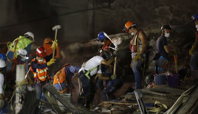 Rescue workers continue into the night searching for survivors inside a felled office building brought down by a 7.1-magnitude earthquake, in the Roma Norte neighborhood of Mexico City, Saturday, Sept. 23, 2017. As rescue operations stretched into day 5, residents throughout the capital have held out hope that dozens still missing might be found alive. (AP Photo/Marco Ugarte)