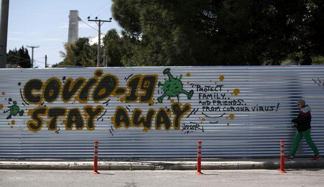 Άνδρας περπατά μπροστά από γκράφιτι για τον κορονοϊό στην Αθήνα