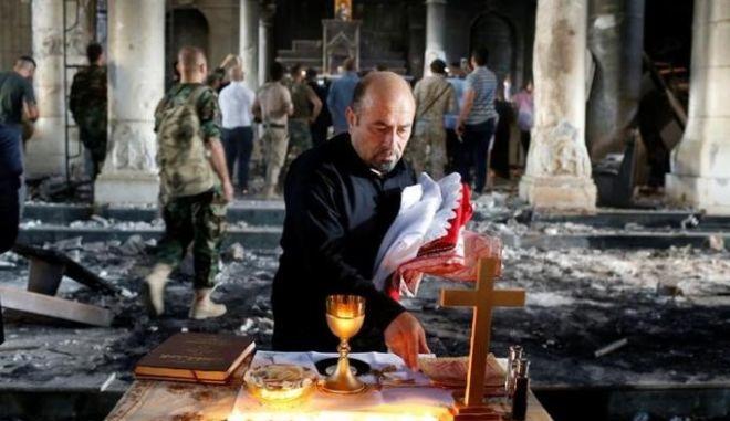 Σε μια μισοκαμένη εκκλησία κοντά στη Μοσούλη οι Χριστιανοί προσεύχονται πάλι