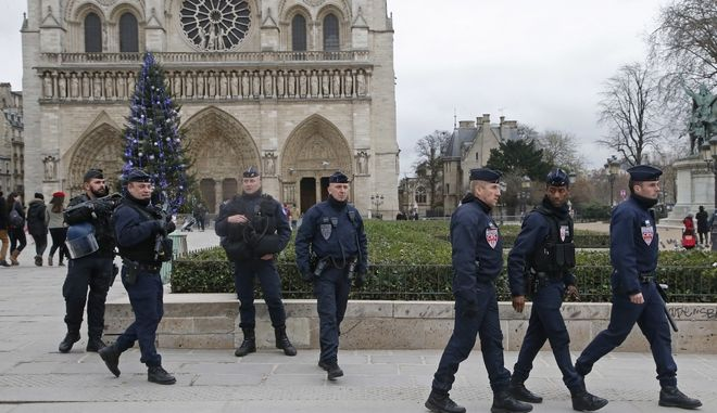 French police officers patrol in front of the Notre Dame cathedral in Paris, France, Sunday, Dec. 24, 2017. France's government is deploying nearly 100,000 police and soldiers for the holiday season as fears of extremist attacks remain high. (AP Photo/Michel Euler)