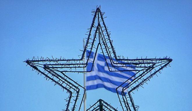 Το αστέρι από χριστουγεννιάτικο δέντρο με φόντο την ελληνική σημαία στην Αθήνα την Τετάρτη 9 Δεκεμβρίου 2015. (EUROKINISSI/ΓΙΩΡΓΟΣ ΚΟΝΤΑΡΙΝΗΣ)