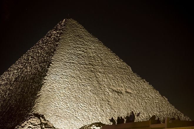 Visitors film the light on the historical site of Giza Pyramids as they celebrate the New Year in Egypt, Monday, Jan. 1, 2018. (AP Photo/Amr Nabil)