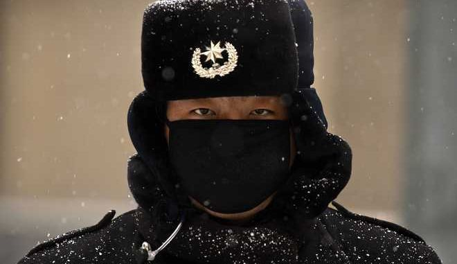 Snow gathers on a Chinese security guard's uniform as he stands outside of an office building on a snowy day in Beijing, Tuesday, Feb. 21, 2017. Winters in China's capital are cold but dry, and snowfall is relatively uncommon. (AP Photo/Mark Schiefelbein)
