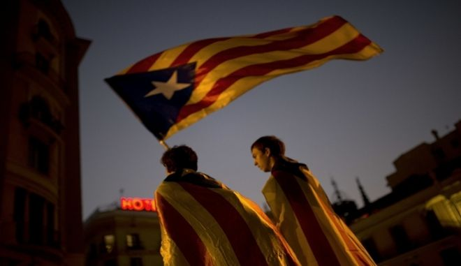 Pro-independence supporters carry an 'Estelada' or independence flag in downtown Barcelona Friday, Oct. 27, 2017. Catalan lawmakers voted Friday to secede from Spain, shortly before Spain's Senate approved a request by the central government to take direct control of Catalonia's affairs.(AP Photo/Francisco Seco)