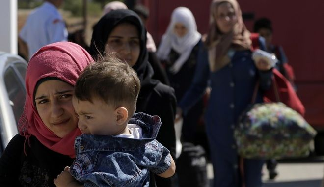 Women and a child migrants from Syria walk towards a refugee camp at Kokkinotrimithia, outside of the capital Nicosia, in the eastern Mediterranean island of Cyprus, on Sunday, Sept. 10, 2017. Cyprus police say a 36-year-old man has been arrested for allegedly driving one of a pair of boats that brought 305 Syrian refugees to the island's northwestern coast. (AP Photo/Petros Karadjias)