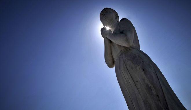 Ο ήλιος φωτίζει τον ουρανό πάνω από το άγαλμα στο Μνημείο Πεσόντων στην Μηλίνα Πηλίου