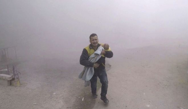 This photo provided by the Syrian Civil Defense group known as the White Helmets, shows what it says is one of its paramedics carrying his wounded son fleeing from the scene of an attack after airstrikes hit a rebel-held suburb near Damascus, Syria, Tuesday, Feb. 6, 2018. Syrian opposition activists said more than one dozen people killed in new airstrikes. (Syrian Civil Defense White Helmets via AP)