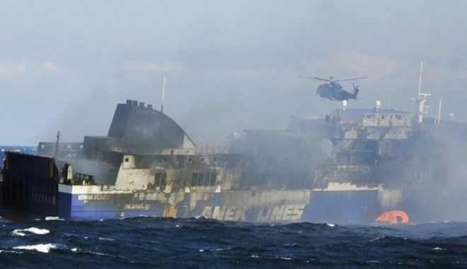 In this image released by the Italian Navy, smoke billows from the Italian-flagged Norman Atlantic that caught fire in the Adriatic Sea, Monday, Dec. 29, 2014. Fighting high winds and stormy seas, helicopter rescue crews on Monday evacuated the last of hundreds of people trapped aboard a Greek ferry that caught fire off Albania. The death toll climbed to eight as survivors told of a frantic rush to escape the flames and pelting rain. The evacuation of the ferry was completed in the early afternoon with the rescue of 427 people, including 56 crew members, said Italy's transport minister, Maurizio Lupi. The original ferry manifest listed 422 passengers and 56 crew members, but Lupi said it was premature to speculate on whether people were still missing. He suggested that there might have been some people who reserved a spot on the ferry but did not board. (AP Photo/Italian Navy, ho)