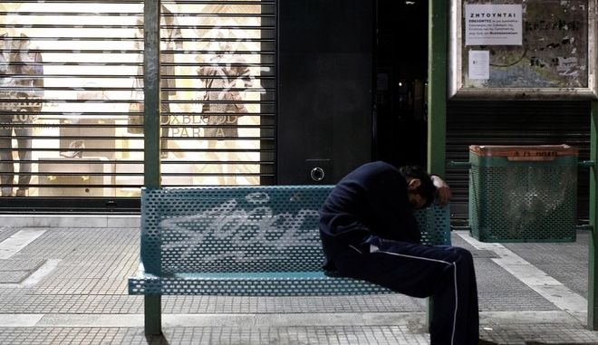 A man sleeps at a bus stop in the city of Thessaloniki, Greece on 19 October 2013. /           ,   19  2013.
