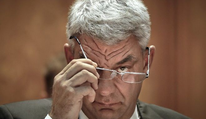 Romanian Premier-designate Mihai Tudose removes his glasses before a parliament vote on the new Romanian government in Bucharest, Romania, Thursday, June 29, 2017. Liviu Dragnea, the chairman of Romania's ruling Social Democratic Party has named the new leftist government, and many ministers kept the jobs held in the previous government, despite being criticized for underperforming.(AP Photo/Vadim Ghirda)