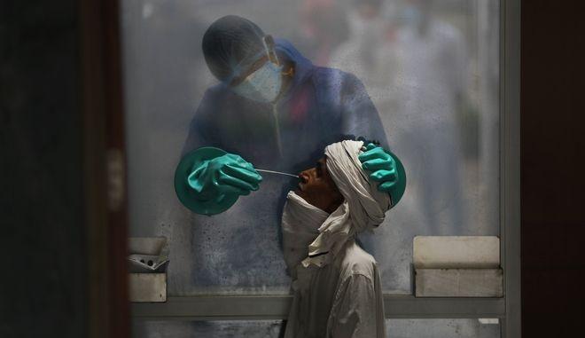 Γιατρός λαμβάνει δείγμα από ασθενή σε νοσοκομείο στην Ινδία