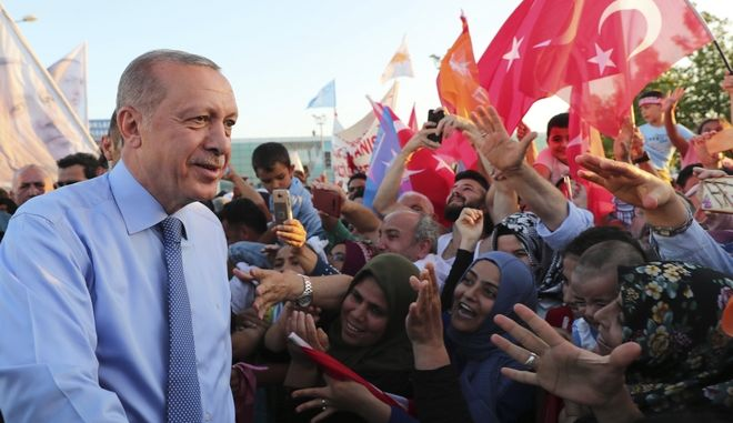 Turkey's President Recep Tayyip Erdogan is greeted by Turkish Cypriots as he arrives in the breakaway Turkish Cypriot northern part of Cyprus' divided capital Nicosia, Tuesday, July 10, 2018. Erdogan visited early Tuesday Azerbaijan and then the breakaway northern part of ethnically divided Cyprus, making his first foreign trips since being sworn in as Turkey's first executive president with sweeping powers. (Presidency Press Service via AP, Pool)