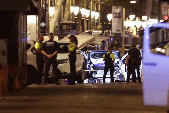 Police officers stand next to the van involved on an attack in La Rablas in Barcelona, Spain, Thursday, Aug. 17, 2017. A white van jumped up onto a sidewalk and sped down a pedestrian zone Thursday in Barcelona's historic Las Ramblas district, swerving from side to side as it plowed into tourists and residents. Police said 13 people were killed and more than 50 wounded in what they called a terror attack. (AP Photo/Manu Fernandez)
