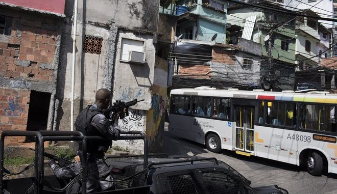 A police officer aims his weapon as he patrols a street during an operation against alleged drug traffickers in the Rocinha slum of Rio de Janeiro, Brazil, Thursday, Jan. 25, 2018. According to the local news, at least nine people were injured during the shootout, including several police officers. (AP Photo/Leo Correa)