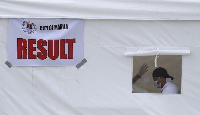 Άνδρας με μάσκα σε σκηνή για τεστ κορονοϊού στη Μανίλα