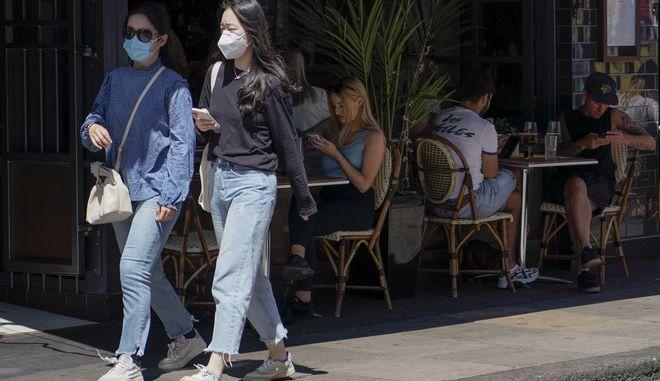 Κόσμος με μάσκες περπατά στην Αγγλία