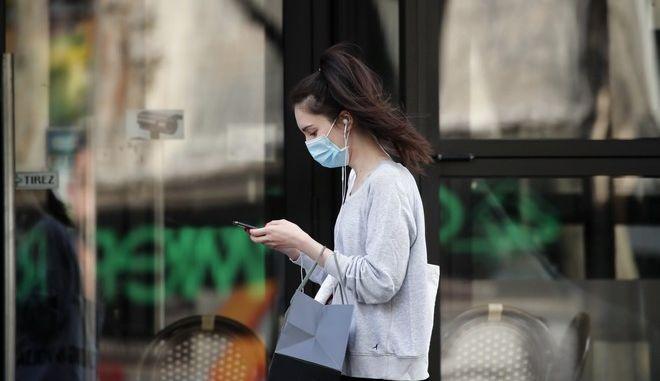 Γυναίκα με μάσκα περπατά στη Γαλλία