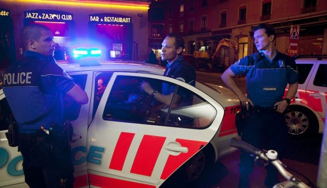 "Switzerland. Geneva. Three police officers arrest a man on the Berne street in the heart of the Paquis neighborhood, known for its nightlife and Red-light district. The policemen have stopped the man while driving under the influence of alcohol. Driving under the influence (DUI), drunken driving, drunk driving, drink driving, operating under the influence, drinking and driving, or impaired driving is the act of driving a motor vehicle with blood levels of alcohol in excess of a legal limit (""Blood Alcohol Content"", or ""BAC""). All policemen are wearing a ballistic vest, bulletproof vest or bullet-resistant vest which is an item of personal armor that helps absorb the impact from knives, firearm-fired projectiles and shrapnel from explosions, and is worn on the torso. Soft vests are made from many layers of woven or laminated fibers and can be capable of protecting the wearer from small-caliber handgun and shotgun projectiles. 01.04.12 © 2012 Didier Ruef"