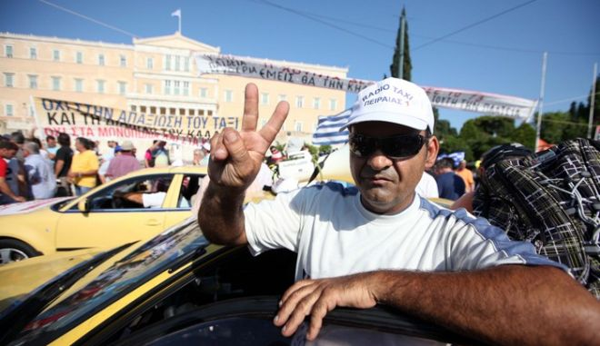 Ιδιοκτήτες ταξί από ολόκληρη την χώρα συγκεντρώνονται έξω από την Βουλή, Τρίτη 26 Ιουλίου, διαμαρτυρόμενοι για την απελευθέρωση του επαγγέλματός τους. (EUROKINISSI // ΓΕΩΡΓΙΑ ΠΑΝΑΓΟΠΟΥΛΟΥ)