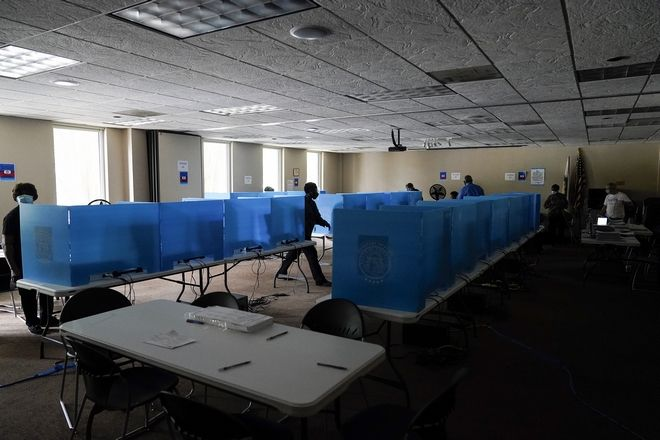 Poll workers walk through dark voting booths during early voting at the Dunwoody Library after Hurricane Zeta knocked out power in the surrounding areas on Thursday, Oct. 29, 2020, in Dunwoody, Ga. (AP Photo/Brynn Anderson)
