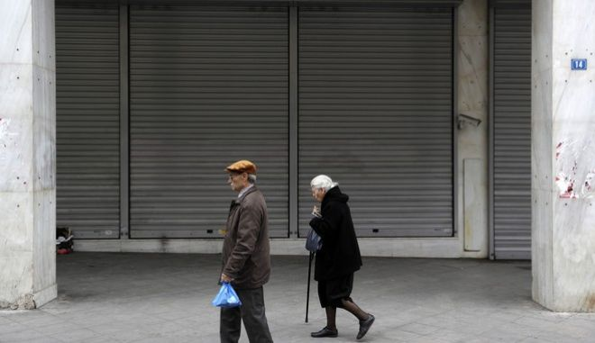 An elderly couple pass a closed bank in Athens, Friday, April 21, 2017. Greeces independent statistics agency says the country has posted a high primary budget surplus in 2016, at 3.9 percent of gross domestic product. (AP Photo/Thanassis Stavrakis)