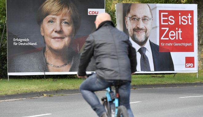 Posters of German Chancellor Angela Merkel, left, and social democrat challenger Martin Schulz, right, for the upcoming general election in Germany are displayed at a street in Essen, western Germany, Thursday, Sept. 14, 2017. General election will held in Germany Sept. 24, 2017. Letters read 'successful for Germany' (CDU) and 'it is time for more fairness'. (AP Photo/Martin Meissner)