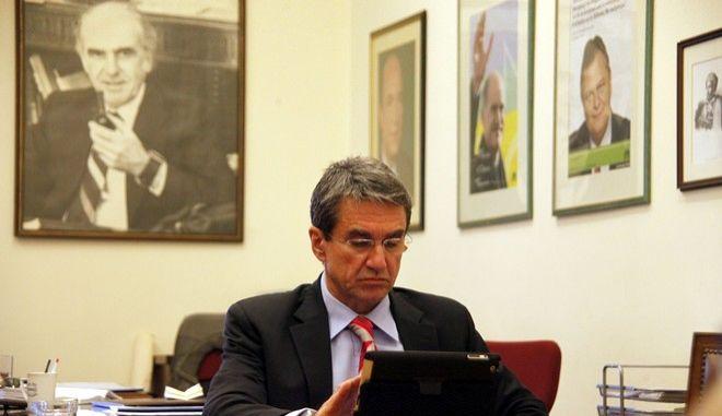 Ο Ανδρέας Λοβέρδος περιεργαζεται το tablet PC του κάτω από το πορτραίτο του ιδρυτή του ΠΑΣΟΚ, Ανδρέα Παπανδρέου (Φωτογραφία αρχείου)