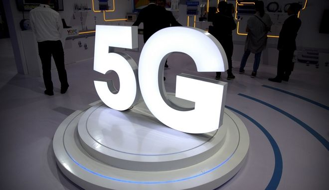 FILE- In this Sept. 26, 2018, file photo visitors stand near a 5G logo at a display the PT Expo in Beijing. AT&T says it will stop advertising its wireless network as 5G Evolution after an industry group determined it was misleading, as it is not, in fact, 5G. (AP Photo/Mark Schiefelbein, File)